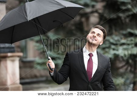 Young man in elegant suit with dark umbrella outdoors