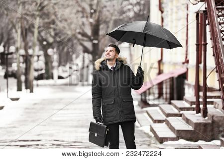 Young man in warm clothes with dark umbrella and briefcase outdoors