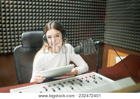 Portrait Of Pretty Young Woman Radio Broadcaster Sitting In Soundproof Recording Studio At Radio Sta