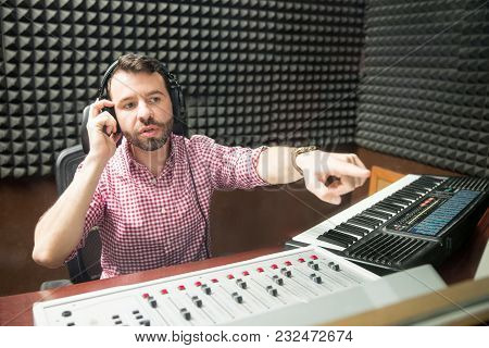 Male Sound Technician Indicating To Radio Host To Correct The Mic Position