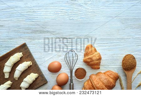 Tasty croissants and products on light background