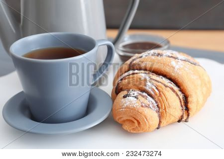 Tasty croissant near cup of coffee on table