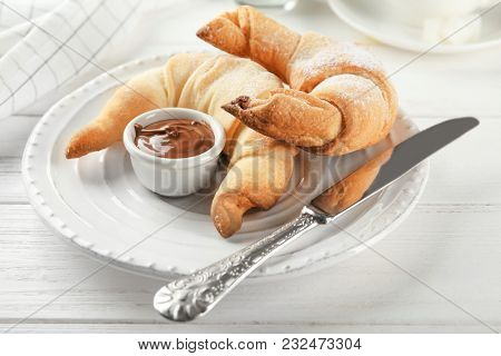 Tasty crescent rolls with chocolate sauce on plate, closeup