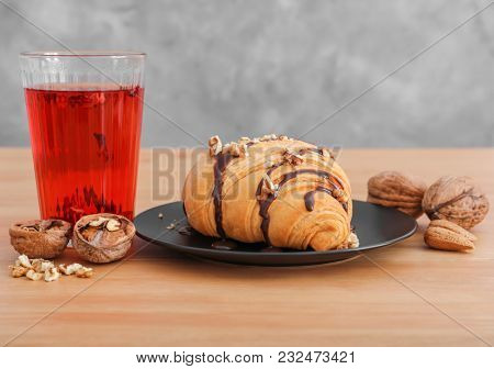 Plate with tasty croissant and glass of tea on table