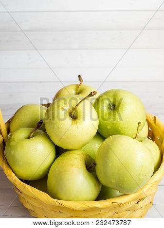 Green Ripe Apples In A Wicker Yellow Basket
