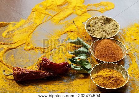 Close Up Of Indian Spices Of Turmeric Powder, Coriander Powder And Chili Powder In  Metal Bowls.