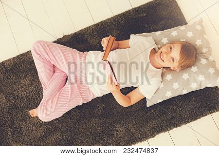 Pleasurable Relax. Top View Of A Happy Pretty Delighted Girl Lying On The Bed And Reading A Book Whi