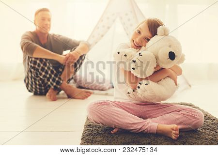 My Best Friend. Happy Cheerful Positive Girl Sitting On The Bed And Hugging Her Fluffy Toy While Res