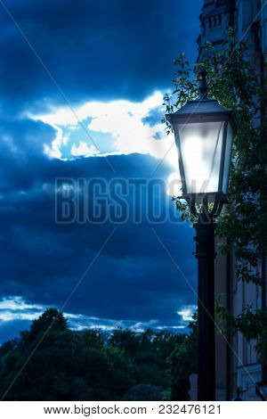 Vintage Iron Street Lamp Shines In The Dark Blue Sky. Blue And Dark Style