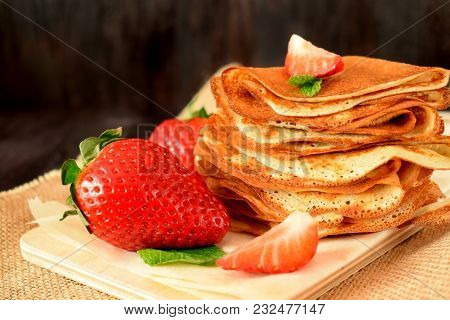 Fresh Strawberries And Golden Crepes On A Wooden Board