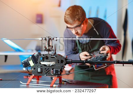 Young Male Engineer Or Technician With Remote Control In His Hands Programs Drone. Focus On Drone