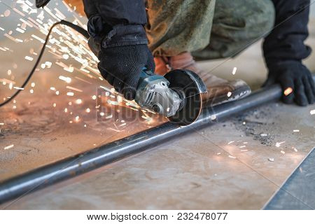 The Builder On The Construction Site Cutting Metal Grinder