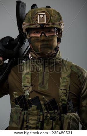 Soldier's picture in camouflage with gun in studio