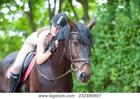 Young Cheerful Teenage Lady-equestrian Tenderly Embracing Her Big Lovely Brown Horse. Vibrant Multic