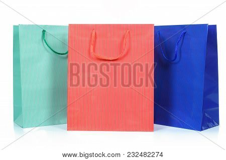 Three Shopping Bags In Different Colors In Close Up And Isolated On A White Background.