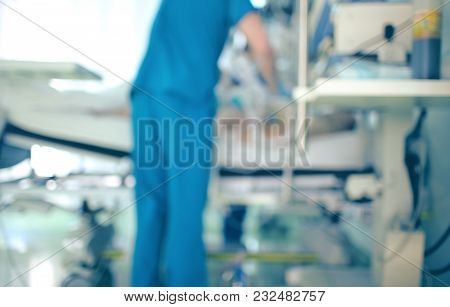 Doctor Assists The Patient In The Intensive Care Unit, Unfocused Background.