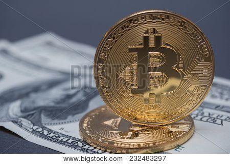 Golden Bitcoins Against The Background Of Dollar Bills