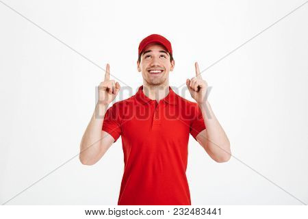 Image of a happy young delivery man in red cap standing pointing isolated over white background. Looking aside.