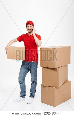 Image of a handsome happy young delivery man in red cap standing with parcel post boxes isolated over white background. Looking camera talking by mobile phone.