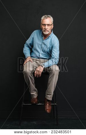 Full length photo of mature stylish man 60s with grey hair and beard sitting on chair in studio and looking on camera isolated over black background