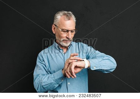Photo of serious gentleman 60s with grey hair wearing eyeglasses looking at his wrist watch with tension isolated over black background