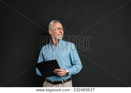Portrait of middle aged man 60s with grey hair and beard looking upward aside holding clipboard with documents isolated over black background