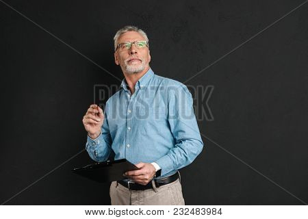 Portrait of middle aged man 60s with grey hair and beard looking upward while holding clipboard with documents isolated over black background