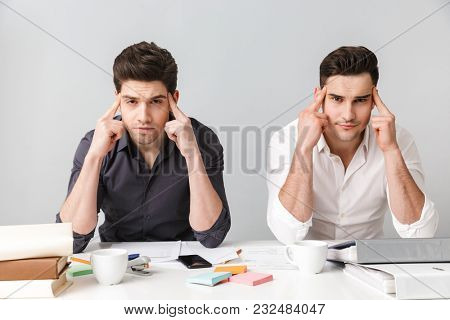 Image of tired two young business men colleagues sitting isolated over grey wall at the table coworking. Looking camera.