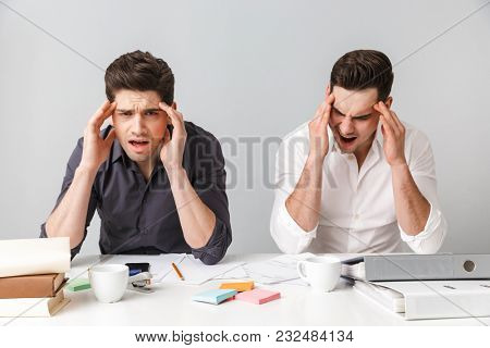 Image of tired two young business men colleagues sitting isolated over grey wall at the table coworking. Looking camera have a painful headache.