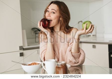 Portrait of a pretty young woman having healthy breakfast while sitting at the table in a kitchen at home in the morning