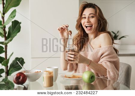 Portrait of a cheerful young woman having tasty breakfast while sitting at the table in a kitchen at home in the morning