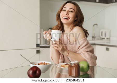 Portrait of a smiling young woman having healthy breakfast while sitting at the table in a kitchen at home in the morning