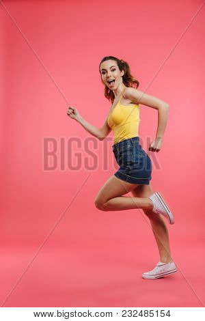 Full length portrait of a happy young girl dressed in summer clothes running and looking at camera isolated over pink background