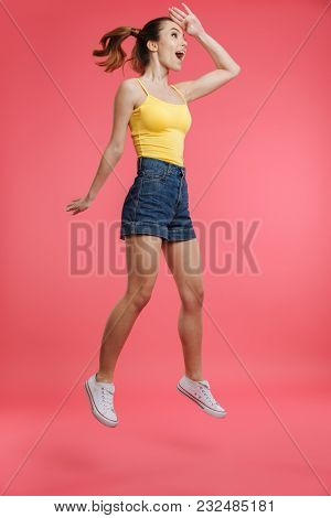 Full length portrait of a happy young girl dressed in summer clothes looking far away while jumping isolated over pink background