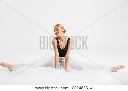 Photo of cheerful cute young woman ballerina sitting stretching gracefully over white wall background isolated. Looking aside.
