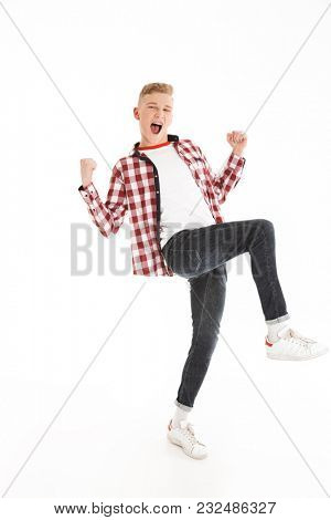 Full length portrait of happy teenage boy wearing plaid shirt smiling and clenching fists on camera like winner or smart pupil isolated over white background
