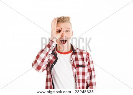 Portrait of a cheerful schoolboy showing ok gesture at his face isolated over white background
