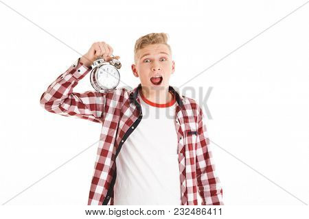 Photo of young hipster man 16y in casual holding alarm clock and emotionally expressing late time isolated over white background