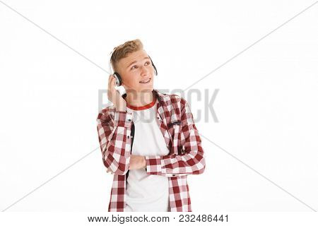 Attractive guy in casual t-shirt 17y wearing braces listening to melody via wireless headphones and looking upward on copyspace isolated over white background