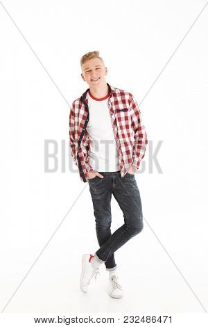 Full length portrait of happy educated teenage boy wearing plaid shirt smiling and looking on camera keeping hands in pockets isolated over white background