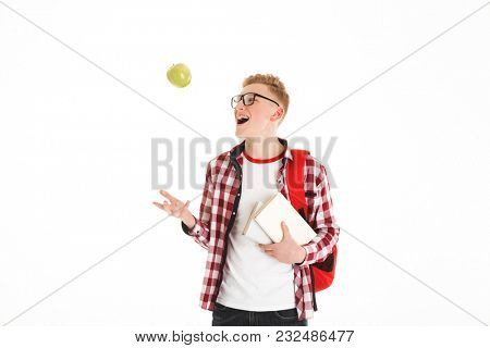 Portrait of a cheerful schoolboy in eyeglasses with backpack holding books and green apple isolated over white background