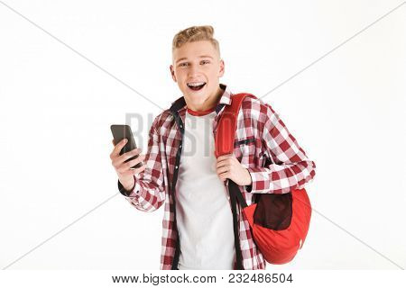 Portrait of a cheerful schoolboy in eyeglasses with backpack using mobile phone isolated over white background
