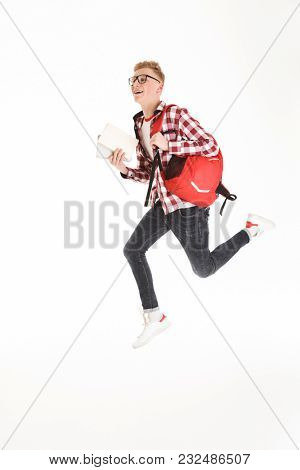 Full length portrait of a joyful schoolboy in eyeglasses with backpack holding books and jumping isolated over white background