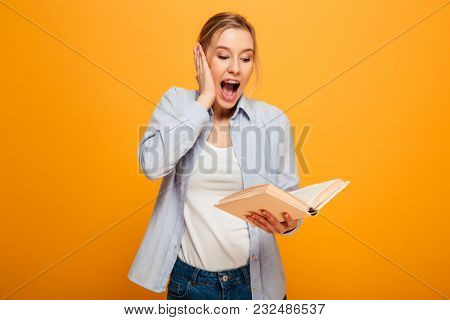 Image of surprised young lady student standing isolated over yellow background reading book. Looking aside.