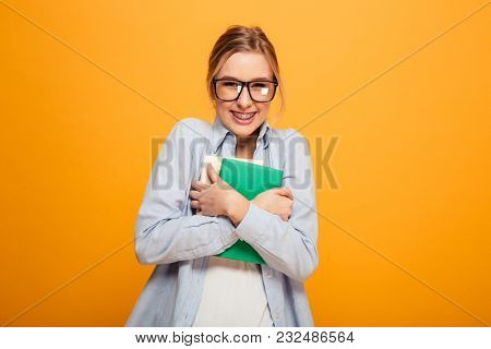 Photo of happy young lady student standing isolated over yellow background. Looking camera holding books.