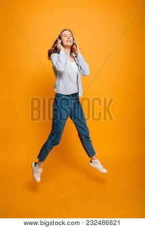 Image of happy young woman jumping listening music isolated over yellow background looking aside.
