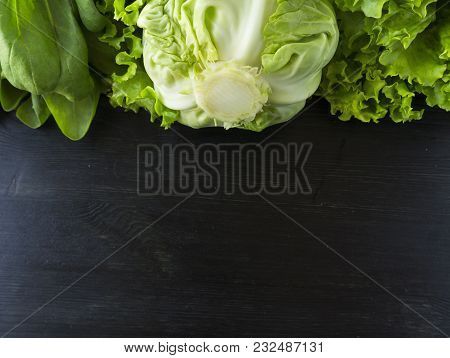 Green Vegetables. Green Vegetable On Black Wooden Background. Spinach, Cabbage And Lettuce. Top View