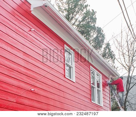 Man On Ladder With Red Shirt Painting Building Red