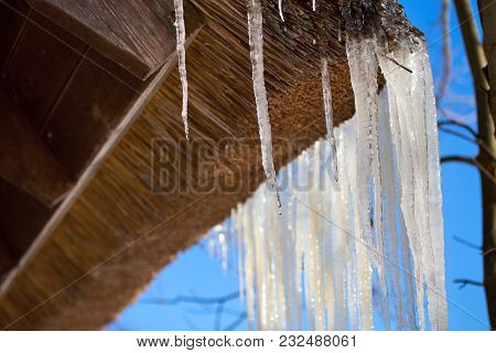 Icicles On Straw Roof Corner Of Rustic House With Selective Focus In Sunny Spring Daylight. Closeup