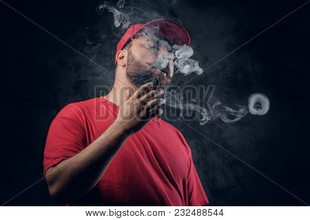 Fatty Bearded Hipster Male In A Red Hip Hop Clothes Smoking A Cigarette On A Grey Background.